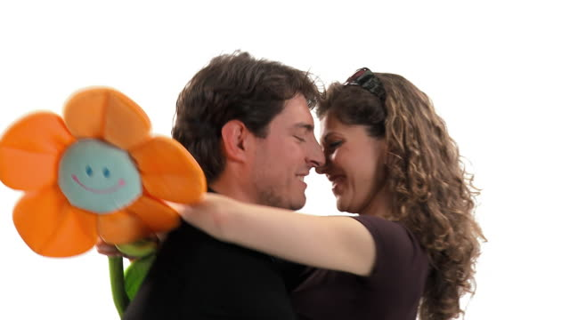 cu studio shot of happy couple kissing, woman holding large artificial flower, vrhnika, slovenia - vrhnika stock videos and b-roll footage