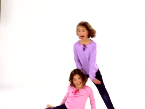 ws, studio shot of identical twin sisters (8-9) fooling around, raleigh, north carolina, usa - identical twin stock videos & royalty-free footage