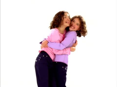 ms, studio shot of identical twin sisters (8-9) hugging, raleigh, north carolina, usa - identical twin stock videos & royalty-free footage