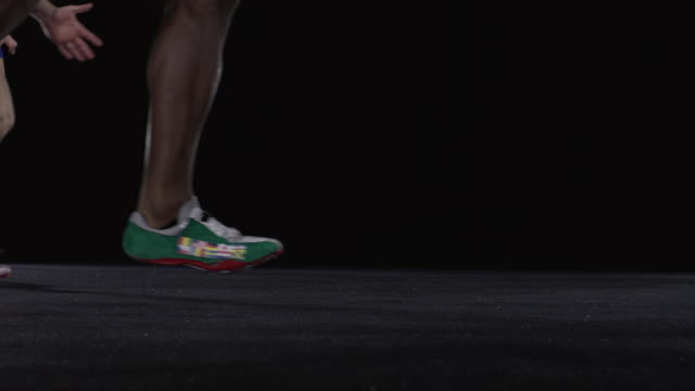 slo mo cu studio shot of legs of four male sprinters running - black background stock videos & royalty-free footage