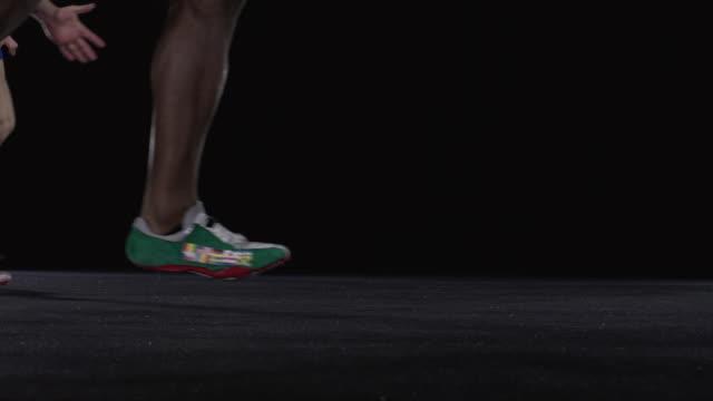 SLO MO CU Studio shot of legs of four male sprinters running