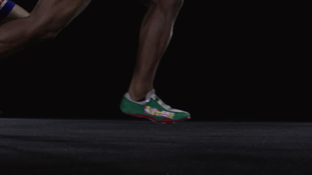 slo mo cu studio shot of legs of four male sprinters running - アシ点の映像素材/bロール