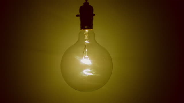 slo mo ms studio shot of light bulb glowing against brown background - brown background stock videos & royalty-free footage