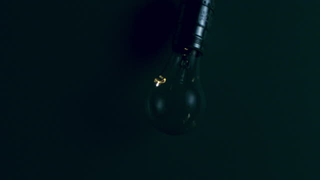 SLO MO MS Studio shot of light bulb swinging against blue background