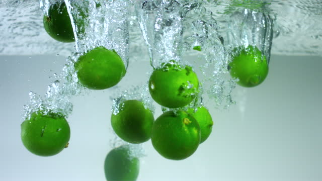 slo mo cu studio shot of limes falling into water - ライム点の映像素材/bロール