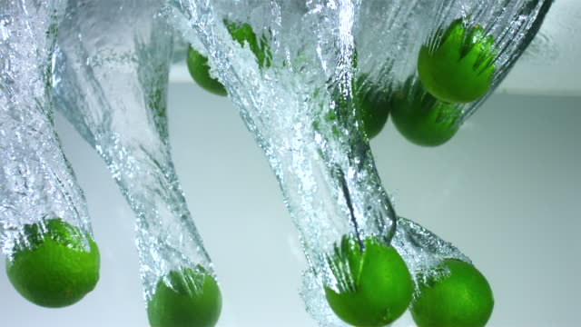 slo mo cu studio shot of limes falling into water - medium group of objects stock videos & royalty-free footage