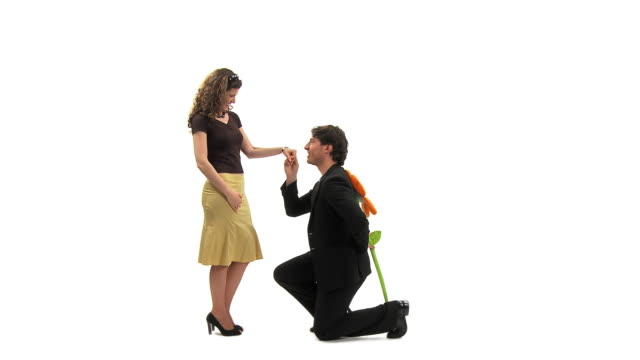 ws studio shot of loving couple, man kneeling and giving woman large artificial flower, vrhnika, slovenia - vrhnika stock videos and b-roll footage