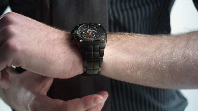 cu studio shot of man fastening black diver's watch, close-up of hands - 腕時計点の映像素材/bロール