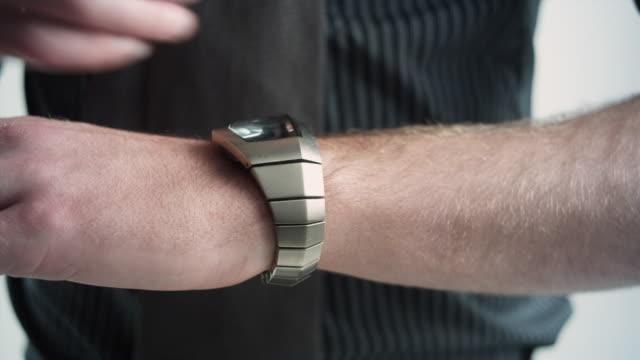 vídeos de stock e filmes b-roll de cu studio shot of man fastening watch, close-up of hands - braço humano