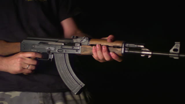 SLO MO, CU, Studio shot of man firing Kalashnikov's automatic rifle, mid section, New York state, USA