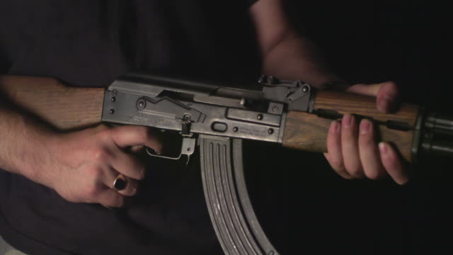 slo mo, cu, studio shot of man firing kalashnikov's automatic rifle, mid section, new york state, usa - mittlerer teil stock-videos und b-roll-filmmaterial