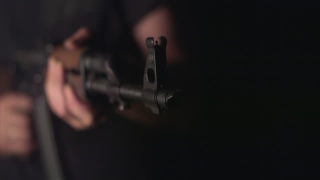 SLO MO, CU, SELECTIVE FOCUS, Studio shot of man firing Kalashnikov's automatic rifle, mid section, New York state, USA