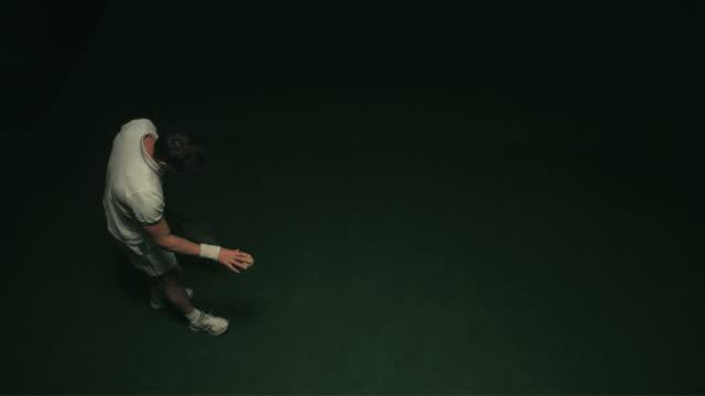 slo mo ws ha studio shot of man serving tennis ball - racquet stock videos & royalty-free footage