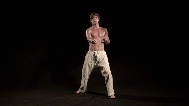 vidéos et rushes de slo mo, ws, studio shot of man training karate, los angeles, california, usa - karaté