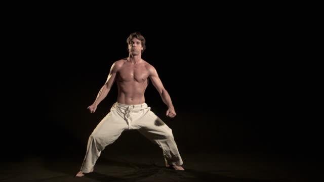 vídeos de stock, filmes e b-roll de slo mo, ws, studio shot of man training karate, los angeles, california, usa - karate