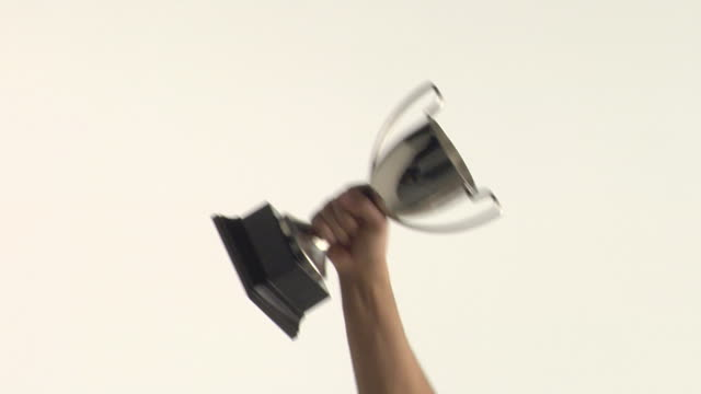 cu studio shot of man's hand raising trophy - auszeichnung stock-videos und b-roll-filmmaterial