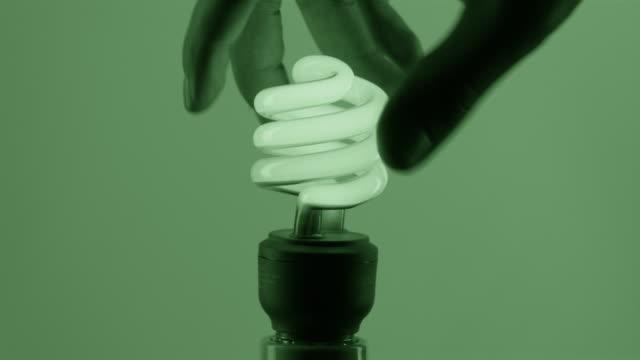 cu studio shot of man's hand screwing green fluorescent light bulb into socket - plug socket stock videos and b-roll footage