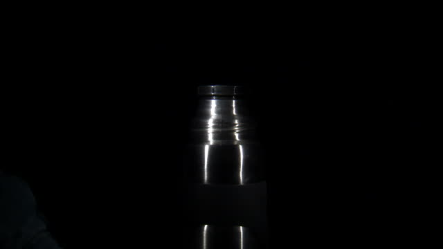 cu studio shot of man's hand screwing lid onto vacuum flask - chiaroscuro stock videos and b-roll footage