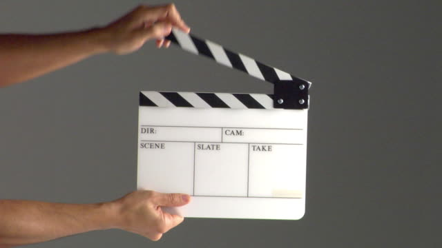 cu studio shot of man's hands clapping film slate - film slate stock videos & royalty-free footage