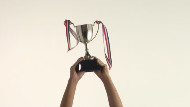 vidéos et rushes de cu studio shot of man's hands raising trophy - award