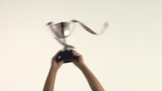 CU Studio shot of man's hands raising trophy