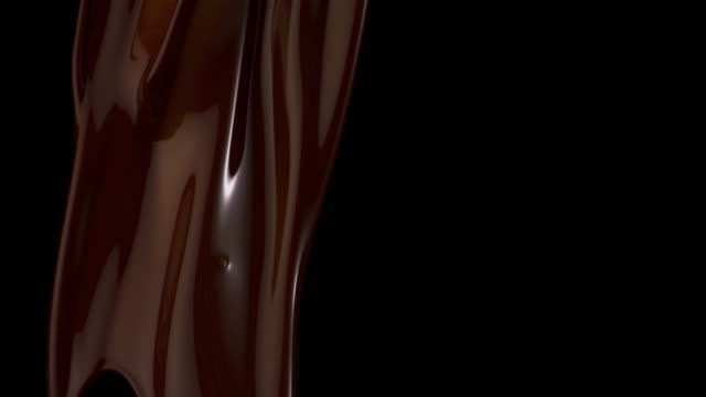 slo mo ms studio shot of molten chocolate being poured against black background - チョコレート点の映像素材/bロール