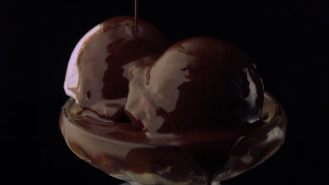 slo mo ms studio shot of molten chocolate being poured on ice cream, cherry on top - on top of stock videos & royalty-free footage