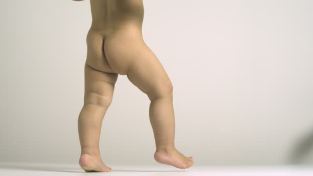 SLO MO, MS, Studio shot of naked baby boy walking, low section