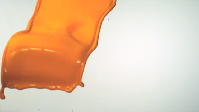 SLO MO, CU, Studio shot of orange paint falling
