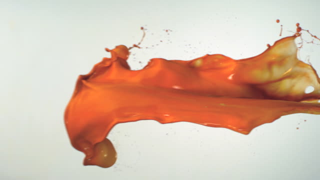 slo mo, cu, studio shot of orange paint splashing - orange colour stock-videos und b-roll-filmmaterial