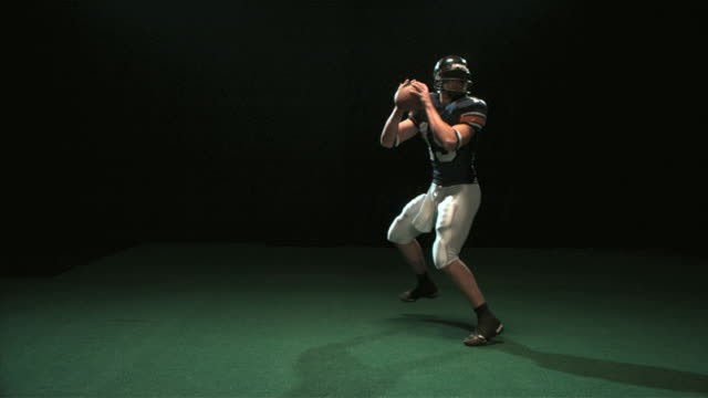 SLO MO WS Studio shot of quarterback throwing ball