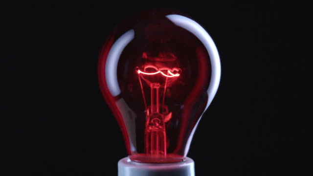 cu focusing studio shot of red incandescent light bulb - incandescent bulb stock videos and b-roll footage