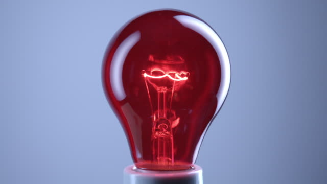 cu studio shot of red incandescent light bulb - incandescent bulb stock videos and b-roll footage