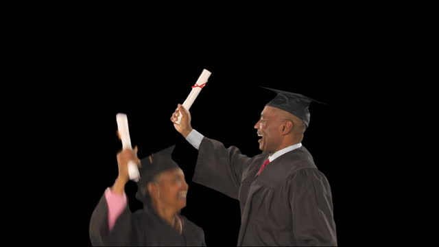 ms, studio shot of senior couple in graduation robes celebrating with diplomas - diploma stock videos & royalty-free footage