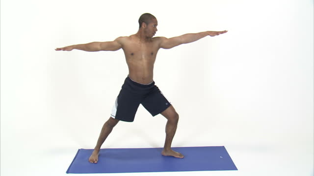 ws studio shot of shirtless young man doing yoga warrior pose and sun salutation pose on blue mat / orem, utah, usa - sun salutation stock videos and b-roll footage
