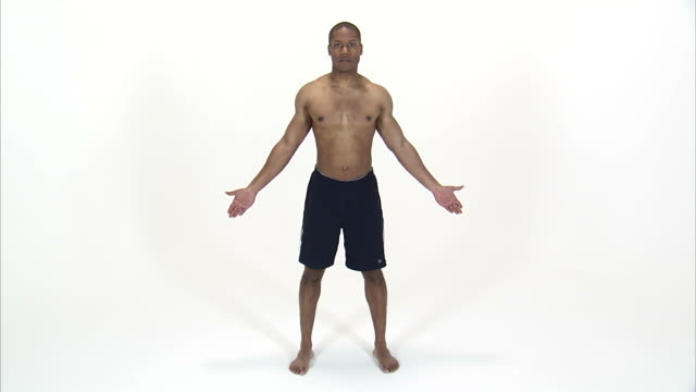 ws studio shot of shirtless young man standing with arms outstretched / orem, utah, usa - ein mann allein stock-videos und b-roll-filmmaterial