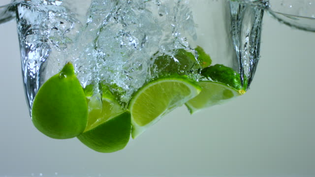 SLO MO CU Studio shot of slices of limes falling into water