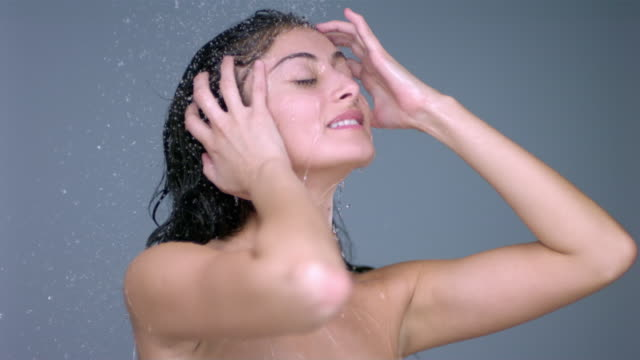 SLO MO CU Studio shot of smiling young woman in shower