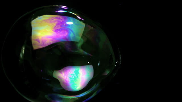 SLO MO CU Studio shot of soap bubble bursting against black background