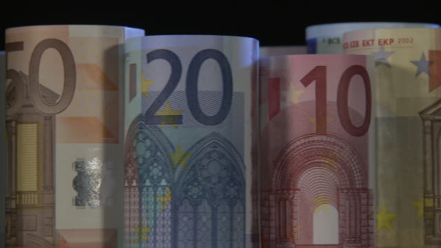 vidéos et rushes de focusing, cu, studio shot of stacked rolls of various euro banknotes turning - billet de banque euro