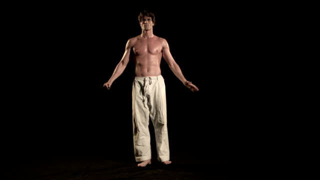 SLO MO, WS, Studio shot of standing in karate pose and bowing, Los Angeles, California, USA