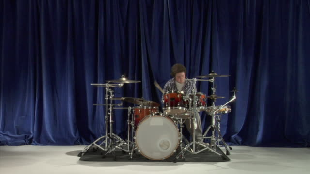 WS Studio shot of teenage boy (16-17) playing drums