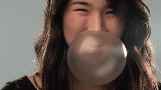 SLO MO CU Studio shot of teenage girl (14-15) blowing and bursting chewing gum bubble
