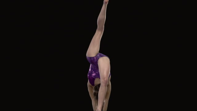 SLO MO WS Studio shot of teenage (16-17) rhythmic gymnast doing cartwheel on balance beam
