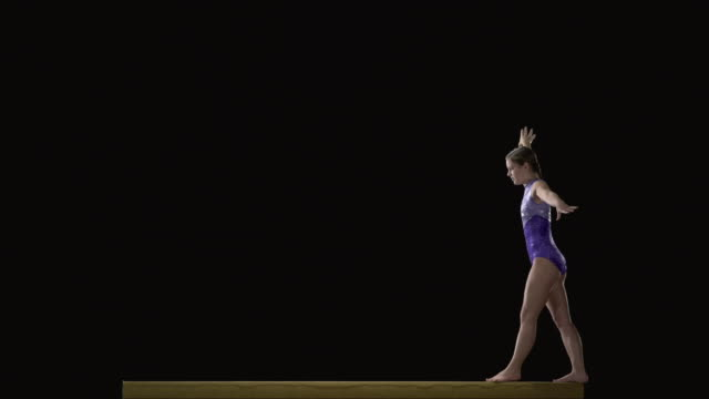 SLO MO WS Studio shot of teenage (16-17) rhythmic gymnast jumping on balance beam