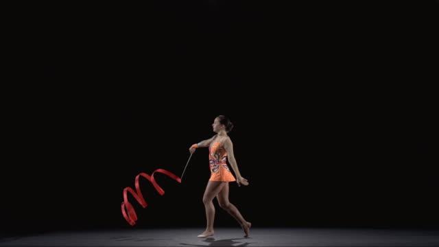 SLO MO WS Studio shot of teenage (16-17) rhythmic gymnast practicing with ribbon