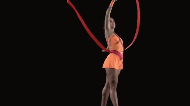 SLO MO MS Studio shot of teenage (16-17) rhythmic gymnast practicing with ribbon