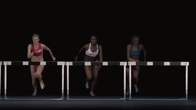 SLO MO WS Studio shot of three female athletes jumping hurdles