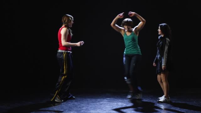WS Studio shot of three young women dancing