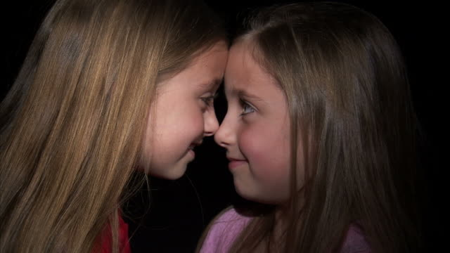 CU Studio shot of twin sisters (8-9) touching noses / Orem, Utah, USA